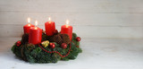 Advent wreath with four red burning candles and christmas decoration on rustic white wood, panorama format with copy space - 182080809