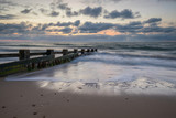 sunrise over groynes in bay