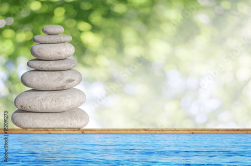 Foto op Canvas Spa Several small beach stone like symbol of balance on wood with green bokeh background