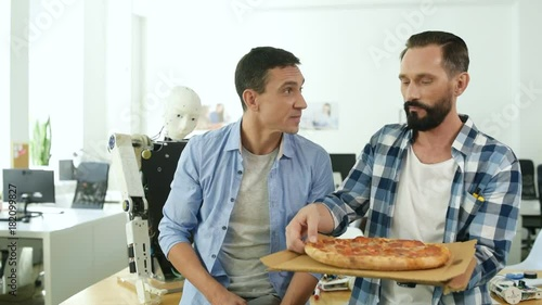 Lunch break. Waist up of pleased colleagues holding tasty pizza while sharing it between each other