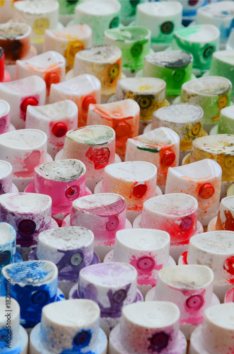 A pattern from a many nozzles from a paint sprayer for drawing graffiti, smeared into different colors. The plastic caps are arranged in many rows forming the color of the rainbow