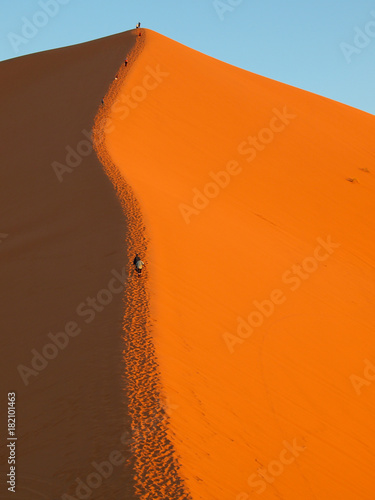 People climbing for the sunset the giant Sahara dunes in Merzouga, Morocco Africa - called the great dune of Merzouga