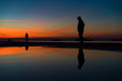 Reflections of People Silhouettes Standing by the Sea, against beautiful after sunset color tones