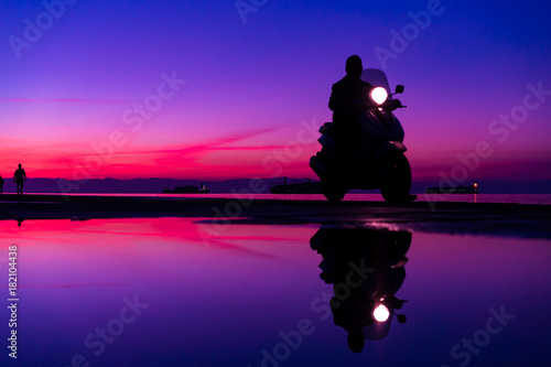 Sihouette of Man with a motorbike; riding by the Sea; against beautiful after sunset Blue and purple color tones - 182104438
