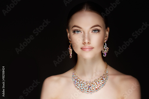 Model in set of jewellery. Luxury girl in shine jewelry from precious stones, diamonds. Beautiful woman in a necklace, earrings and big ring. Beauty and accessories.