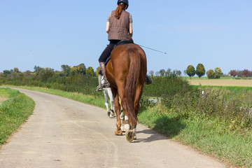 two ladies riding horse on a sunny september day