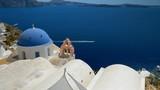 Panning high angle shot of blue dome church on the steep cliff, Aegean Sea, Santorini Island, Greece - 182132651