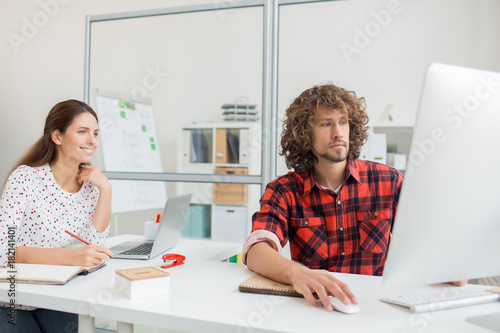 Two young designers studying online course for beginners in office