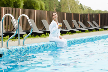 Young woman with juice enjoying her solitude at spa resort © pressmaster