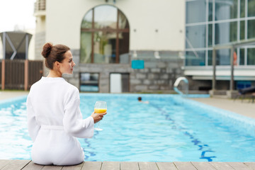 Rear view of young restful female spending day by swimming pool © pressmaster
