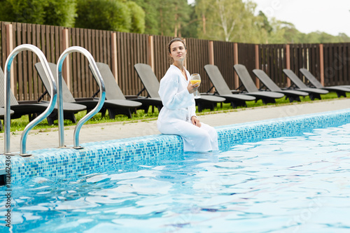 Young woman with juice enjoying her solitude at spa resort