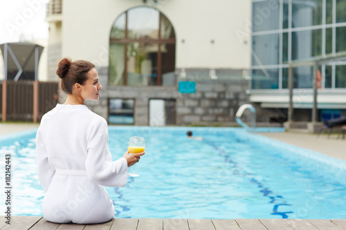 Rear view of young restful female spending day by swimming pool
