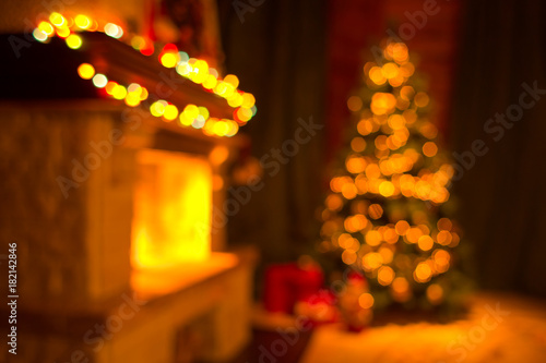 Blurred living room interior with fireplace and decorated christmas tree