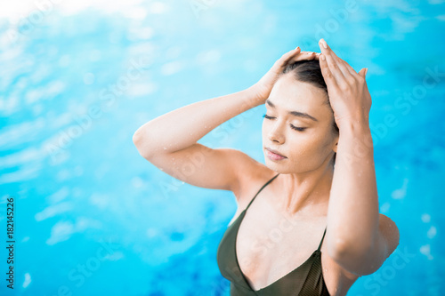 Fotobehang Spa Woman with waterdrops on her skin touching her wet hair while enjoying spa vacation