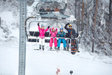 Parents with children in the ski chair  lifting up the ski terrain