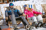 Man and woman skiers sitting in sun lounger