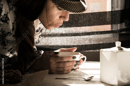 Papiers peints The Trend girl, blowing hot tea, at the breakfast table, in profile