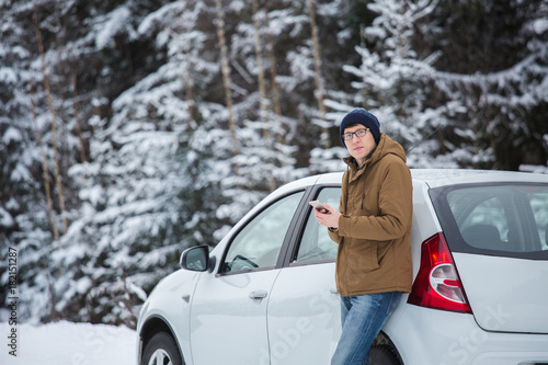 Young man is standing next the car on a winter road. Cold weather, snow-covered trees in the winter forest. Man looking at the camera and holds mobile phone in his hands. Winter travel.