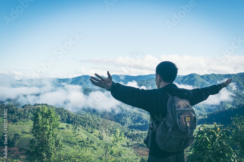 Carefree happy man enjoying nature on top of mountain cliff with sunrise Poster
