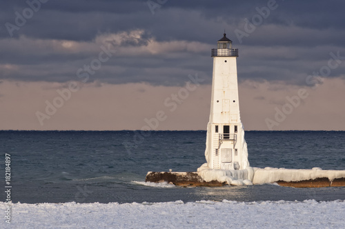 Fotobehang Vuurtoren Frankfort, Michigan lighthouse on the Great Lakes covered in snow and ice