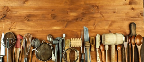 Old kitchen utensils on a wooden board. Sale of kitchen equipment. Chef's tools. © martinfredy