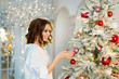 beautiful slender happy young girl with makeup standing near Christmas tree