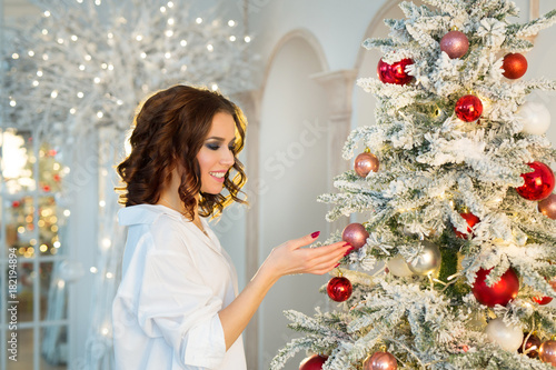 beautiful slender happy young girl with makeup standing near Christmas tree Poster