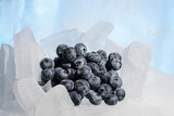 Fresh blueberries are frozen on cold blue ice