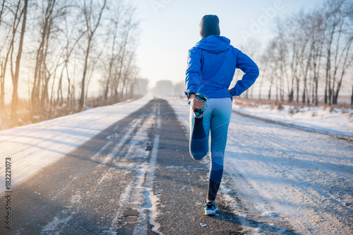 Foto op Canvas Jogging Runner stretching in winter Park. A healthy way of life.
