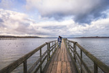 Woman walking on a deck at sunset - Lovely young woman walking alone on a long wooden bridge, over the famous Chiemsee lake, enjoying the breeze and the cold sunset of November, in Germany. - 182231469