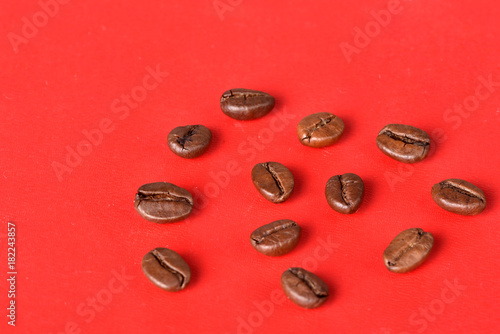 Poster Koffiebonen Texture of grains of caffeine.Place for text.Roasted coffee beans.Advertising for coffee.Coffee beans on a red background.