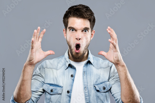 Angry young man screaming over gray background.