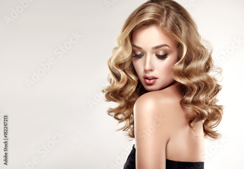 Beautiful girl blonde hair with an elegant hairstyle , hair wave ,curly hairstyle .
