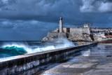 Cuba, Havana. Waves Breaking on the Malecon Sea Front. El Morro Fort in Background