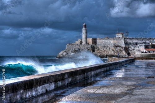 Deurstickers Havana Cuba, Havana. Waves Breaking on the Malecon Sea Front. El Morro Fort in Background