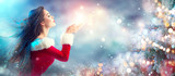 Christmas scene. Sexy Santa. Brunette young woman in party costume blowing snow over holiday blurred background - 182266025