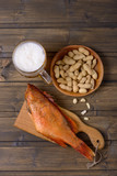 Beer mug and fish with peanuts on wooden table - 182266047