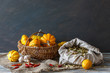 Still life in a rustic style: autumn harvest. Pumpkins and red peppers on a wooden table. Natural light from a window.