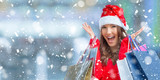 Christmas shopping. Attractive happy girl with credit card and shopping bags in santa hat. Snowy atmosphere. - 182277460
