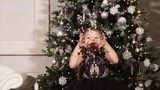 Slow motion shot of a little girl blowing colorful confetti during Christmas celebration - 182280408