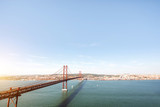 Wide angle landscape view on the Tagus river and the famous 25th of April Bridge in Lisbon city, Portugal