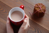 Female hands hold a red mug of cocoa on the wooden table - 182280616