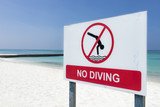 Close up of no diving sign against the backdrop of the clear blue sea - 182281498