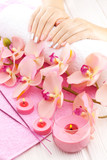 beautiful pink manicure with orchid, candle and towel on the white wooden table.