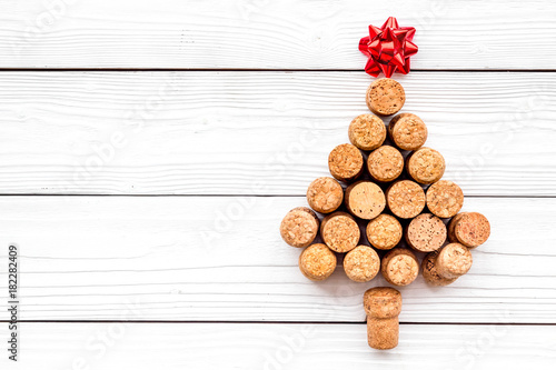 Corks of wine bottles in shape of new year spruce on black background top view