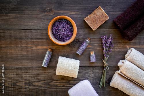 Floral foot spa with lavender. Spa salt, sponge, soap, towel on dark wooden background top view copyspace