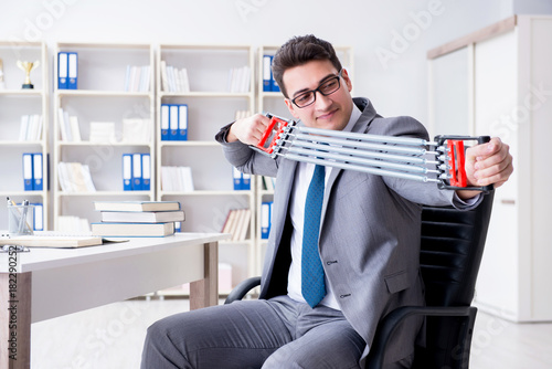 Sticker Young businessman exercising with elastic expander in office