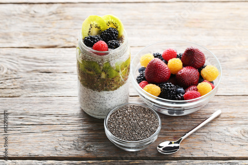 Staande foto Zuivelproducten Chia pudding with berries in bottle on grey wooden table