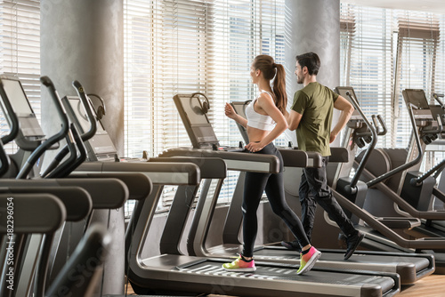 Frau und Mann laufen im Fitnessstudio auf dem Laufband