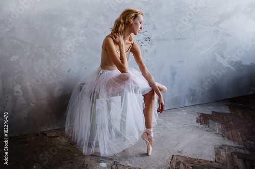 Young and slim ballet dancer is posing in a stylish studio with big windows